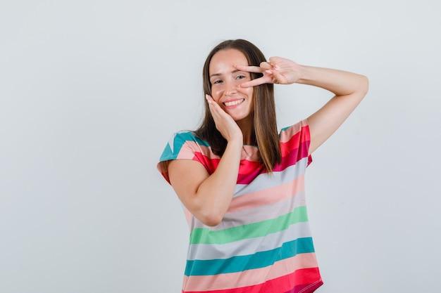 Jovem mulher mostrando o sinal-v perto do olho em uma camiseta e parecendo com sorte, vista frontal.