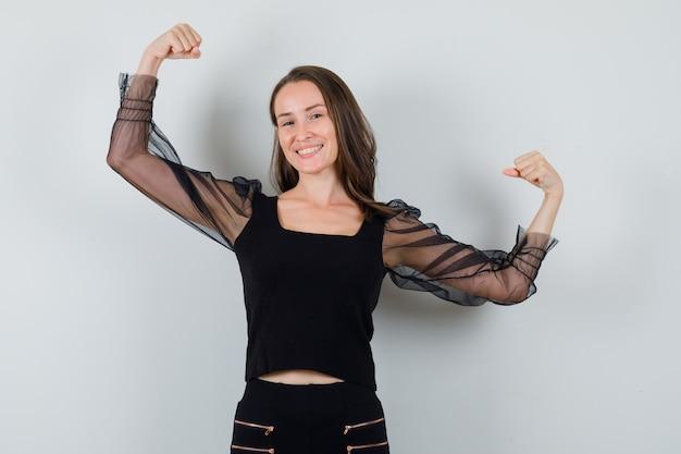 Jovem mulher mostrando os músculos em uma blusa preta e calça preta e parece confiante. vista frontal.