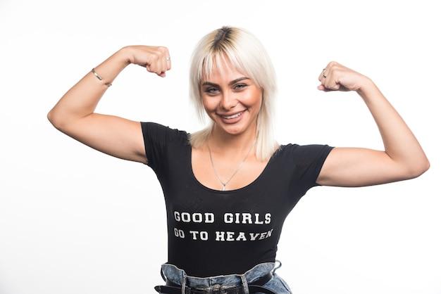 Jovem mulher mostrando os músculos na parede branca com uma expressão feliz.