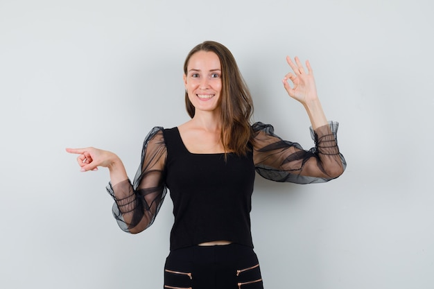 Jovem mulher mostrando sinal de ok e apontando para a esquerda em blusa preta e calça preta e parecendo feliz, vista frontal.