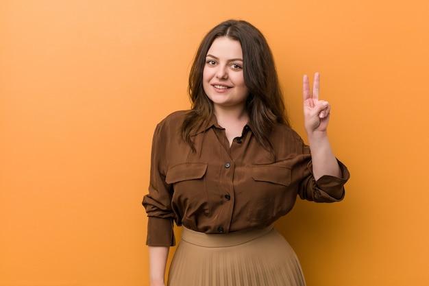 Jovem mulher mostrando sinal de vitória e sorrindo amplamente