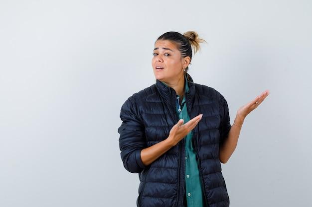 Jovem mulher mostrando um gesto de boas-vindas na camisa, jaqueta e parecendo confusa, vista frontal.