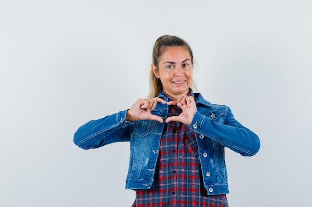 Jovem mulher mostrando um gesto de coração na camisa, jaqueta e olhando feliz, vista frontal.