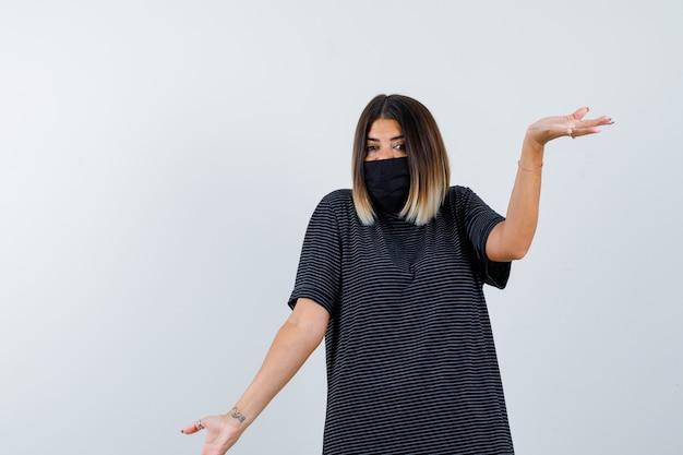 Jovem mulher mostrando um gesto de impotência em um vestido preto, máscara preta e parecendo perplexo. vista frontal.