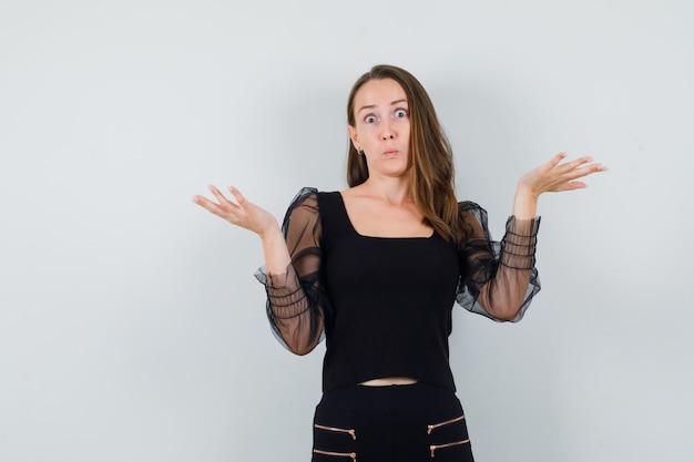 Jovem mulher mostrando um gesto desamparado em blusa preta e calça preta e parecendo surpresa. vista frontal.