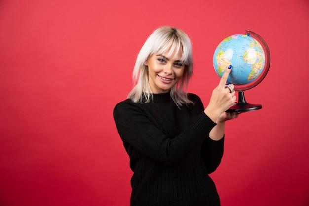 Jovem mulher mostrando um globo sobre um fundo vermelho. foto de alta qualidade