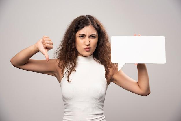 Jovem mulher mostrando um polegar para baixo e segurando um pôster branco em branco. foto de alta qualidade