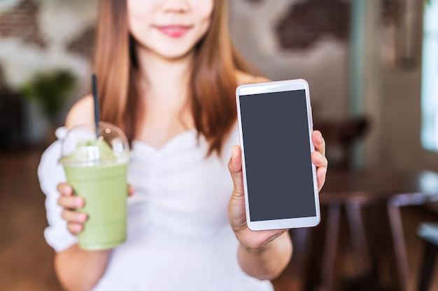 Jovem mulher mostrando um smartphone de tela vazia com espaço de cópia enquanto toma uma bebida em uma cafeteria