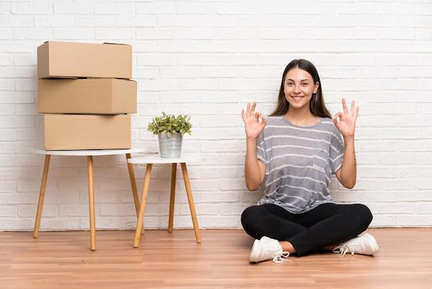 Jovem, mulher, movendo-se em nova casa entre caixas, mostrando um sinal de ok com os dedos