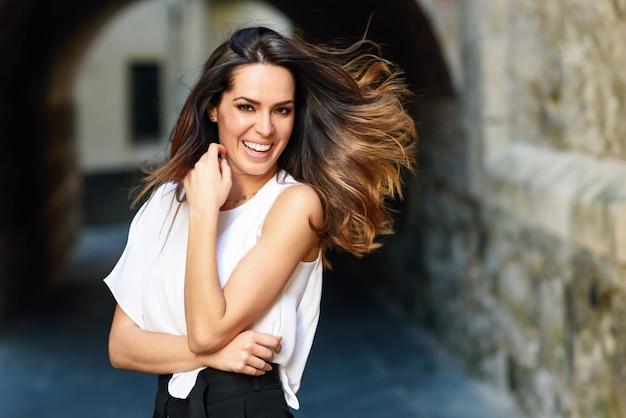 Jovem mulher movendo seus cabelos longos em meio urbano.