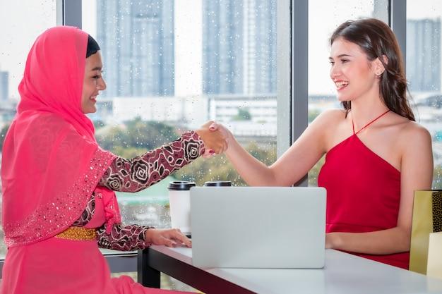 Jovem mulher muçulmana, apertando a mão com amizades caucasianos, sentado perto de sacolas de compras