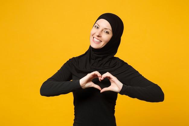 Jovem mulher muçulmana árabe com roupas pretas de hijab, mostrando forma de coração com as mãos, isolada na parede amarela, retrato. conceito de estilo de vida do islã religioso de pessoas.