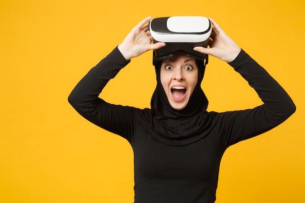 Jovem mulher muçulmana árabe em roupas pretas de hijab assistindo no fone de ouvido da realidade virtual de vr isolada no retrato de parede amarela. conceito de estilo de vida religioso de pessoas.