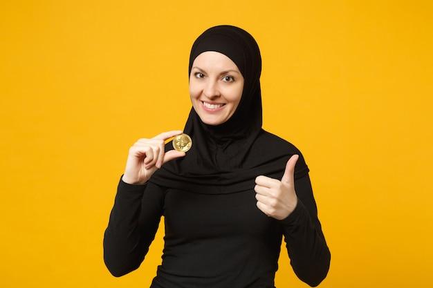 Jovem mulher muçulmana árabe em roupas pretas de hijab segura na mão segurando a moeda da moeda bitcoin isolada no retrato de parede amarela. conceito de estilo de vida religioso de pessoas.