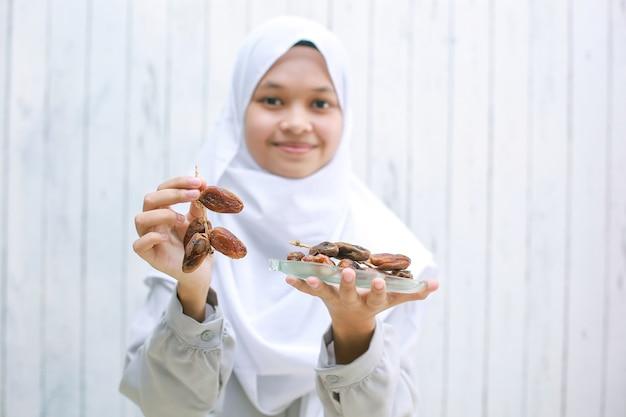 Jovem mulher muçulmana asiática sorrindo e oferecendo tâmaras na mão enquanto segura as tâmaras no prato