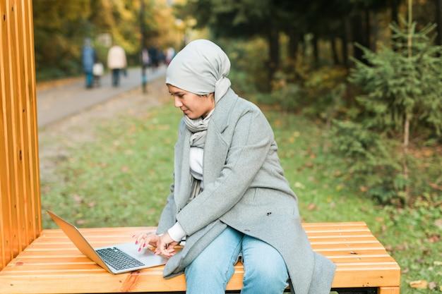 Jovem mulher muçulmana asiática usando laptop no outono parque educação online, compras online e social