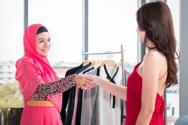Jovem mulher muçulmana bonita, apertando a mão com amizades caucasianos, sentado perto de sacolas de compras e tablet desfrutando de compras na cafeteria.