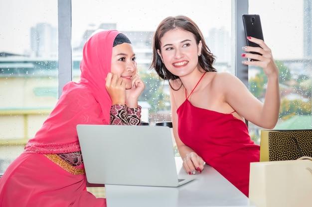 Jovem mulher muçulmana bonita selfie com amizades caucasianos, sentado perto de sacolas de compras e tablet desfrutando de compras na cafeteria.