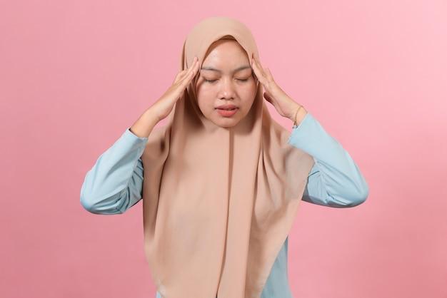 Jovem mulher muçulmana com dor de cabeça, isolada em um fundo rosa