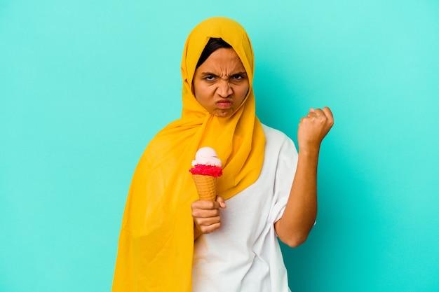Jovem mulher muçulmana comendo um sorvete isolado em um fundo azul, mostrando o punho para a câmera, expressão facial agressiva.