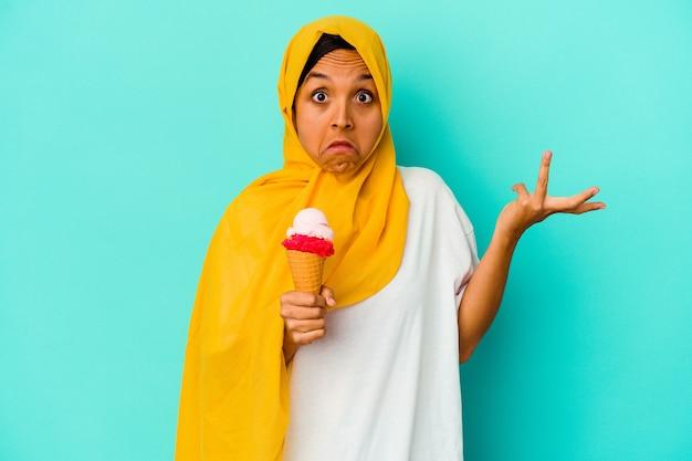 Jovem mulher muçulmana comendo um sorvete nos ombros azuis encolhe os ombros e abre os olhos confusos.