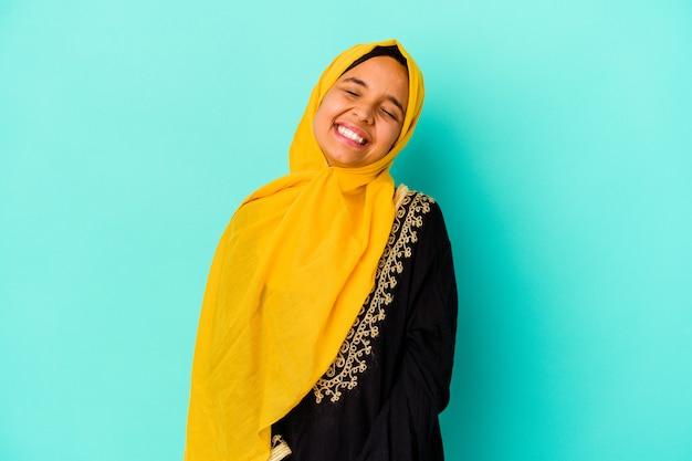 Jovem mulher muçulmana em azul relaxada e feliz rindo, pescoço esticado, mostrando os dentes.