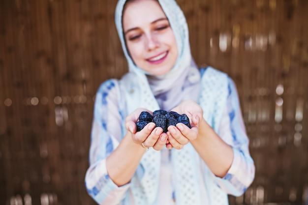 Jovem mulher muçulmana em hijab segurando tâmaras nas mãos