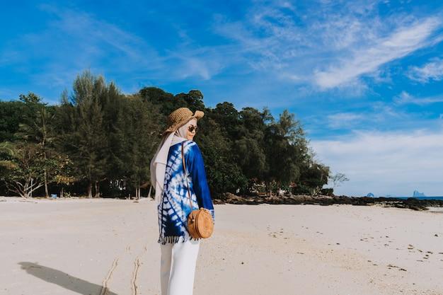Jovem mulher muçulmana em pé na praia. verão e conceito do curso, turista asiático no tempo de verão.