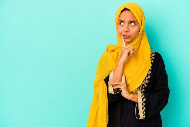 Jovem mulher muçulmana isolada na parede azul olhando de soslaio com expressão duvidosa e cética