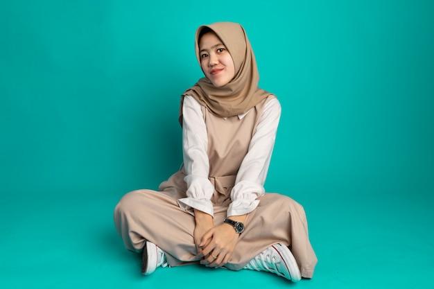 Jovem mulher muçulmana moderna vestindo roupas casuais da moda e hijab. menina elegante sentada