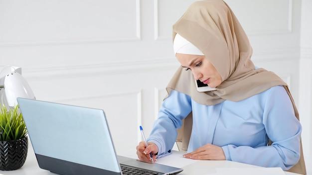 Jovem mulher muçulmana no hijab está falando com o cliente no celular, explicando a situação, fazendo anotações em papel e olhando para a tela do laptop em seu local de trabalho no escritório.
