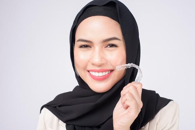 Jovem mulher muçulmana segurando o aparelho invisalign em estúdio, saúde odontológica e conceito ortodôntico.