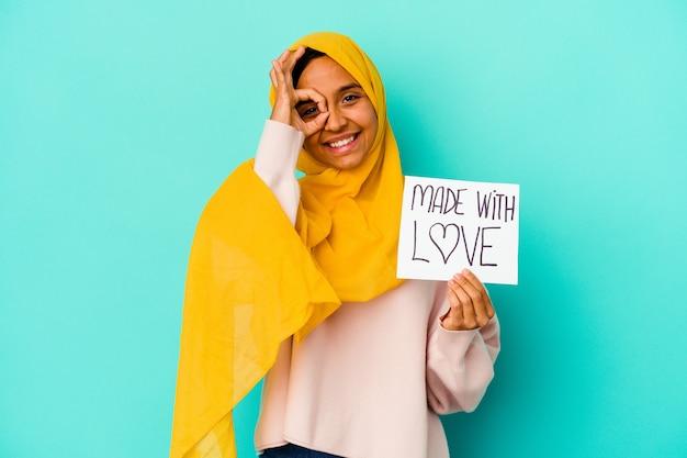 Jovem mulher muçulmana segurando um cartaz de amor isolado na parede azul, animado, mantendo o gesto ok no olho.