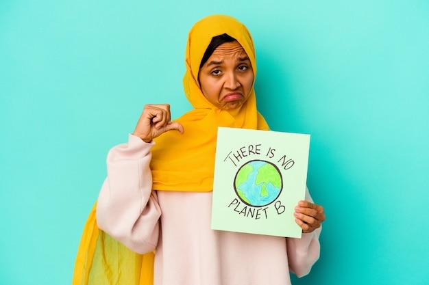Jovem mulher muçulmana segurando um cartaz de não há planeta b isolado em um fundo azul sente-se orgulhosa e autoconfiante, exemplo a seguir.