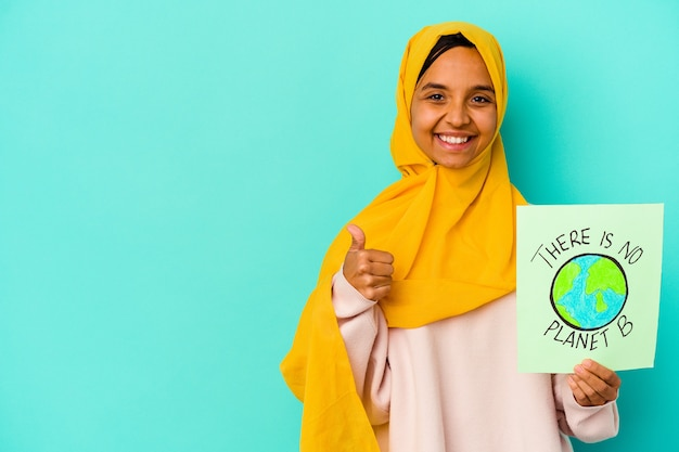 Jovem mulher muçulmana segurando um cartaz de não há planeta b isolado em um fundo azul, sorrindo e levantando o polegar