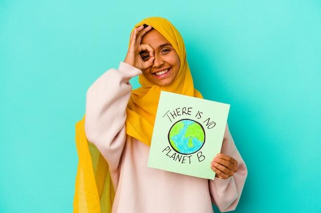 Jovem mulher muçulmana segurando um cartaz de não há planeta b isolado na parede azul animado, mantendo o gesto ok no olho.