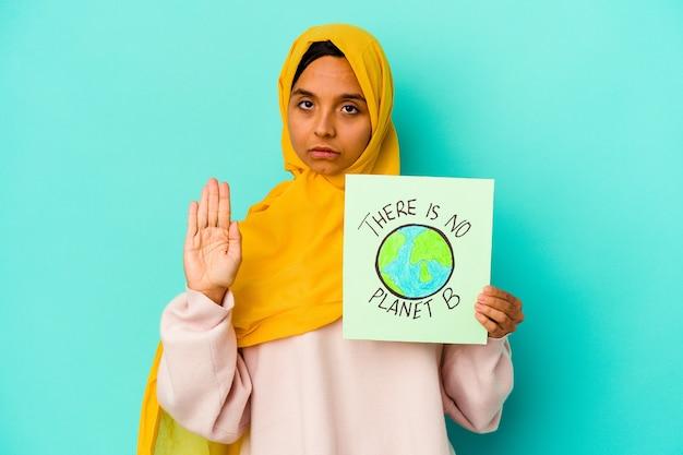 Jovem mulher muçulmana segurando um cartaz de não há planeta b isolado na parede azul em pé com a mão estendida mostrando a placa de pare
