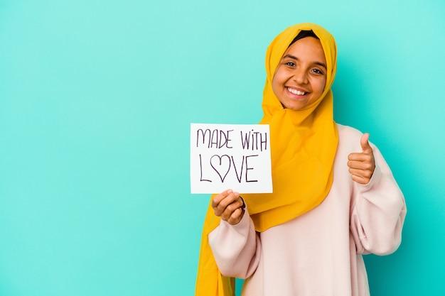 Jovem mulher muçulmana segurando um cartaz feito com amor, isolado na parede azul, sorrindo e levantando o polegar