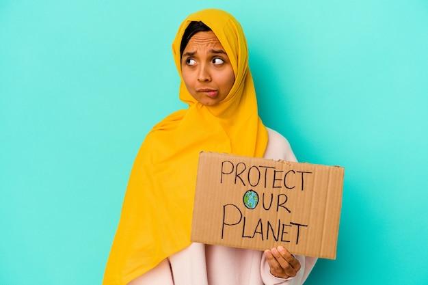 Jovem mulher muçulmana segurando um proteger nosso planeta isolado em um fundo azul confuso, sente-se em dúvida e inseguro.