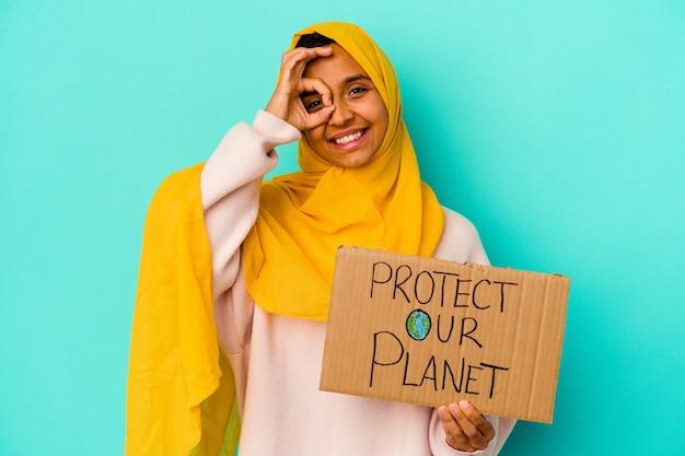 Jovem mulher muçulmana segurando um proteger nosso planeta isolado sobre fundo azul animado, mantendo o gesto ok no olho.