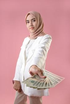 Jovem mulher muçulmana segurar dinheiro