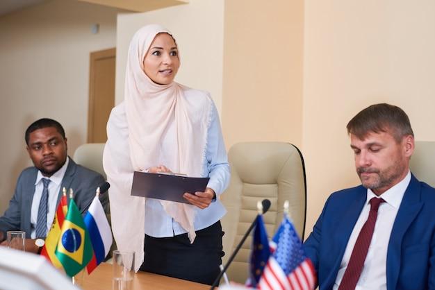 Jovem mulher muçulmana usando hijab fazendo uma reportagem em uma conferência em frente a uma plateia no corredor