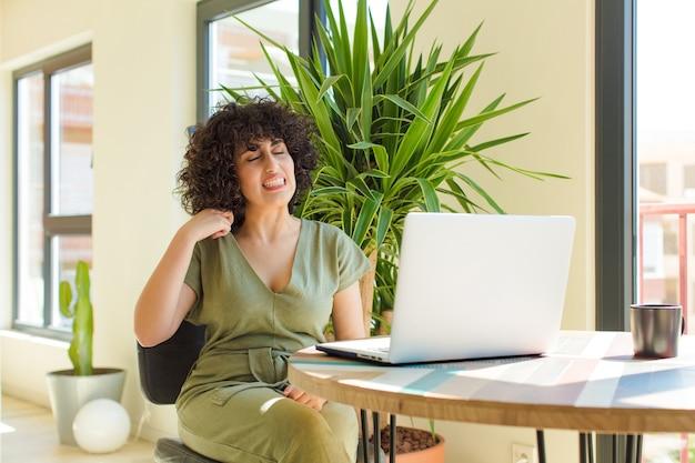 Jovem mulher muito árabe com um laptop sobre uma mesa.