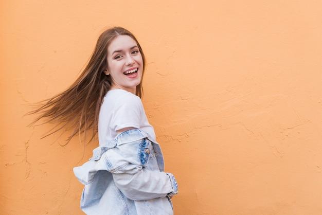 Jovem mulher muito bonita que levanta perto do fundo colorido da parede