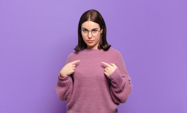 Jovem mulher muito casual apontando para si mesma com um olhar confuso e interrogativo, chocada e surpresa por ser escolhida