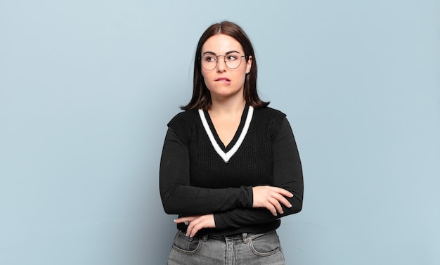Jovem mulher muito casual duvidando ou pensando, mordendo o lábio e sentindo-se insegura e nervosa, procurando copiar o espaço ao lado