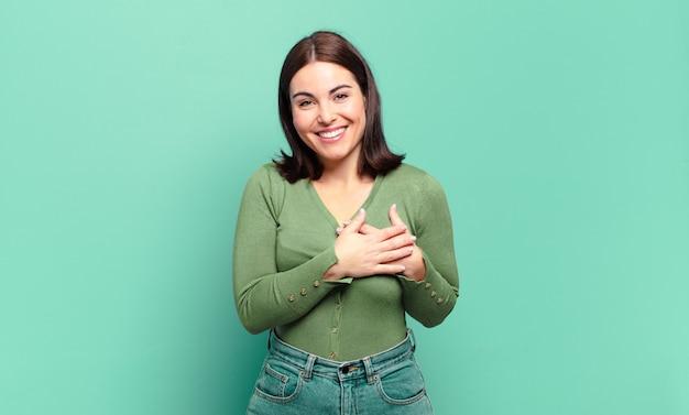 Jovem mulher muito casual se sentindo romântica, feliz e apaixonada, sorrindo alegremente e segurando o coração de mãos dadas