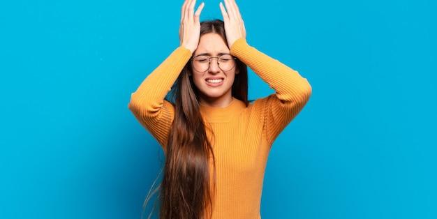 Jovem mulher muito casual sentindo-se estressada e ansiosa, deprimida e frustrada com uma dor de cabeça, levantando as duas mãos à cabeça