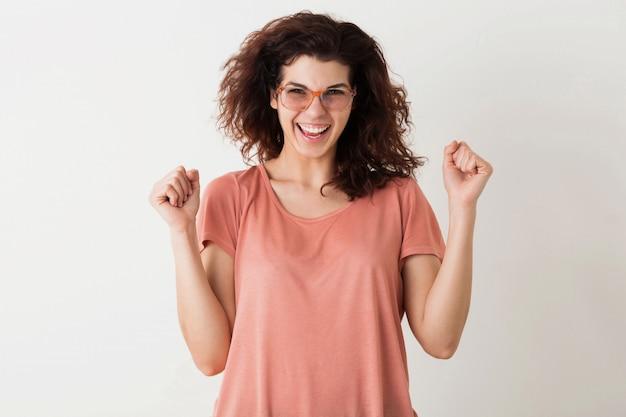 Jovem mulher muito elegante de óculos, segurando as mãos em gesto de vitória, cerrando os punhos, emocional, vencedor, cabelos cacheados, rindo, emoção positiva, feliz, isolado, camiseta rosa