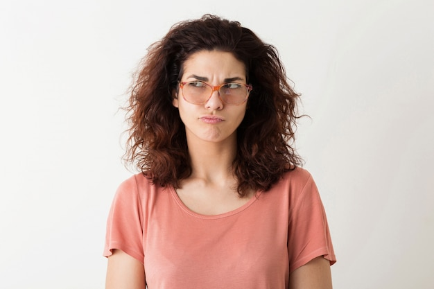 Jovem mulher muito elegante em óculos pensando, expressão do rosto pensativo, cabelos cacheados, tendo problema, emoção engraçada, isolado, camiseta rosa, estudante, franzindo a testa